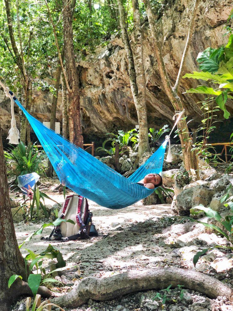 a girl lying in a hammock in the jungle in Cenote Dos Ojos near Tulum Mexico