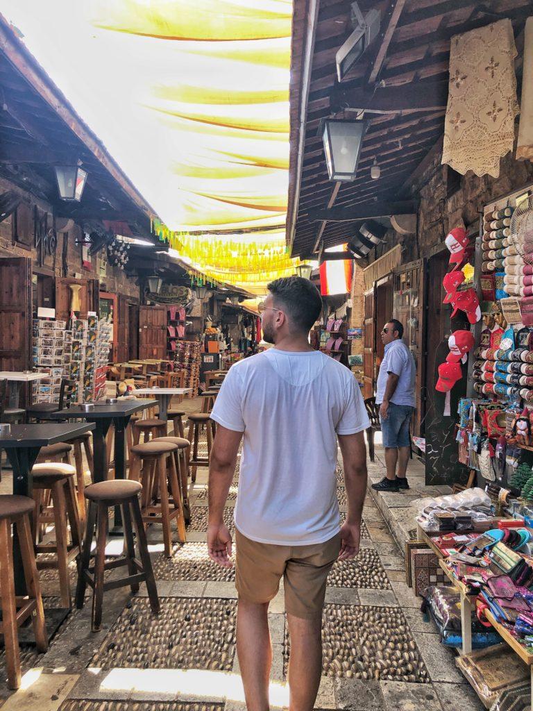 Man walking in a street full of shops in a souk in Byblos Lebanon