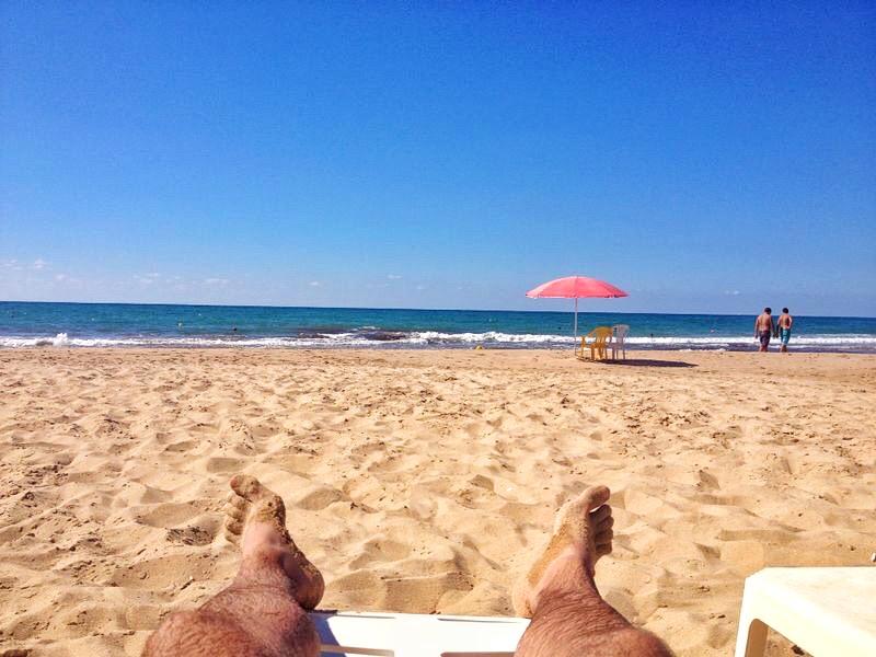 man lying on the beach looking at the sea in Rmeileh Lebanon
