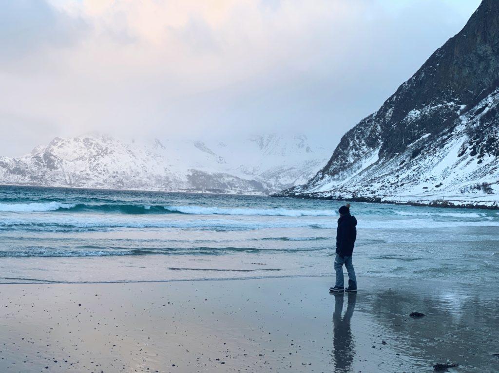 Man walking in the sand in Grøtfjord fjord in Norway